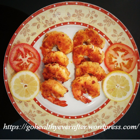 restaurant-style breaded prawns with slices of lemon and tomatoes in a ceramic plate