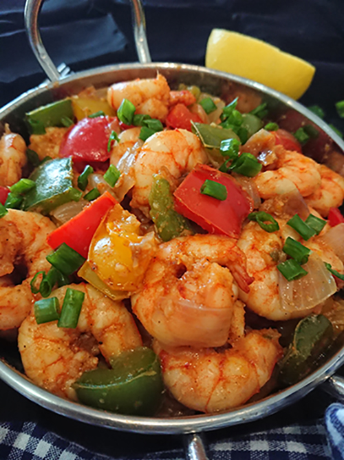close-up view of garlic prawns with red, green and yellow peppers in a silver bowl