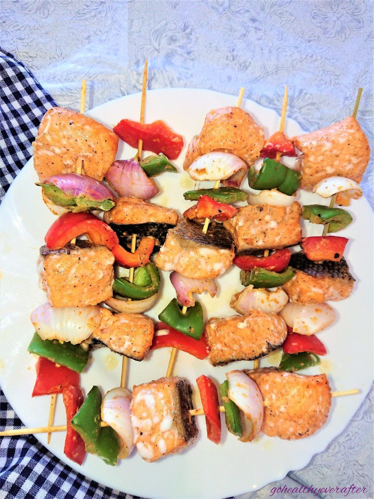 baked salmon kababs on skewers with onions and peppers