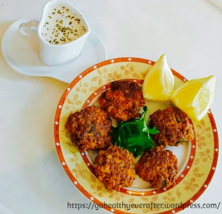 fish patties garnished with lemon wedges and cilantro in a ceramic plate and a cup of yogurt cashew dip