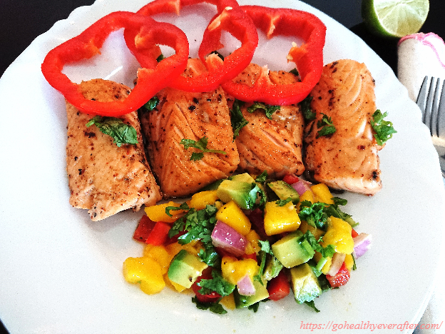 Pan seared salmon with mango-avocado salsa in a white ceramic plate