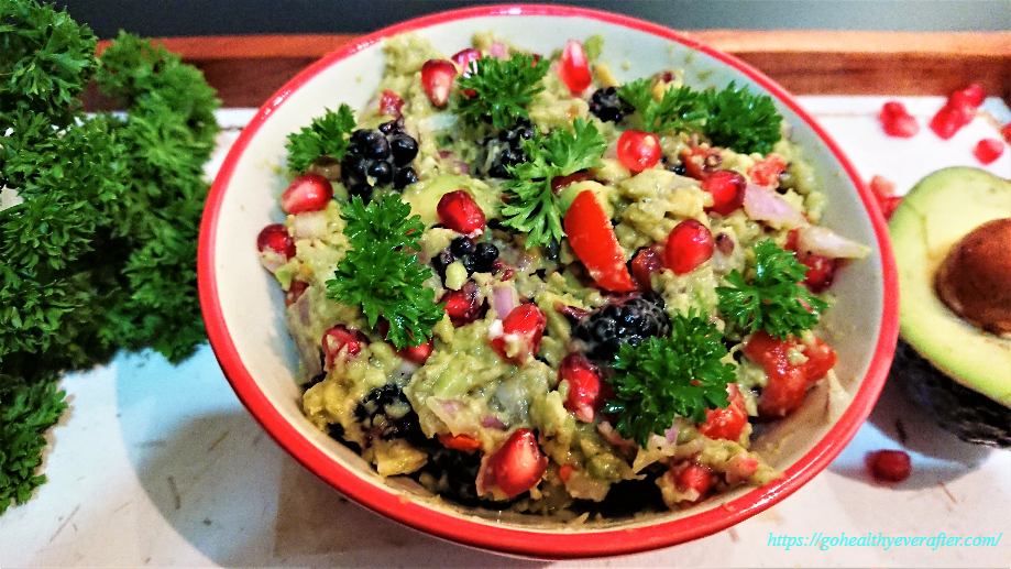 guacamole with berries, pomegranate and parsley in a ceramic bowl