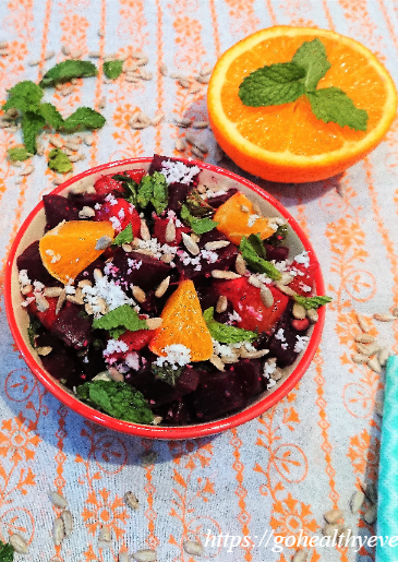 beet orange salad in a ceramic bowl and a cut orange with some mint leaves.