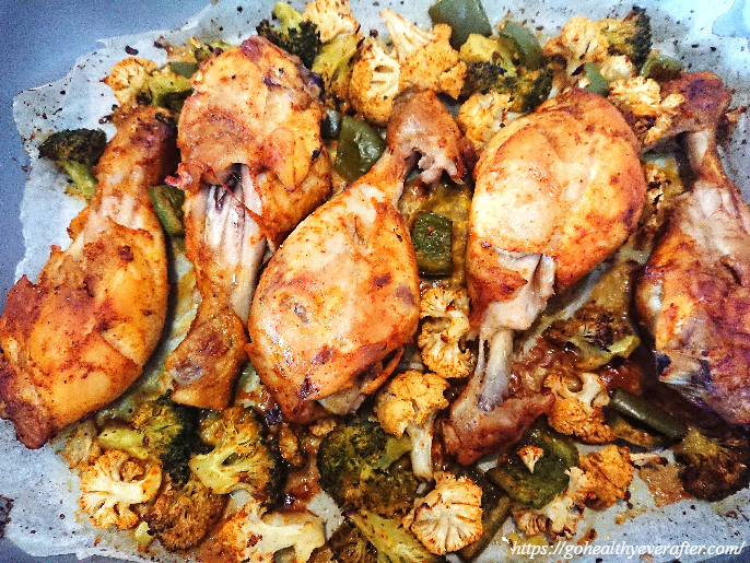 close-up view of oven-baked buttermilk chicken drumsticks and vegetables.