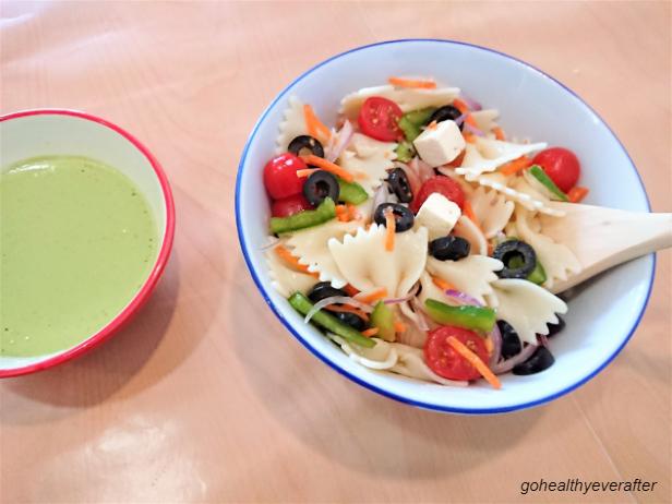 pasta salad and mint yogurt sauce in different bowls