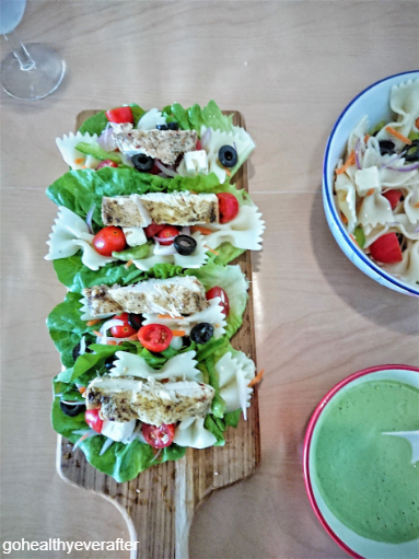 lettuce wraps with pasta salad, pan-roasted chicken breast and bowls of mint yogurt sauce and pasta salad