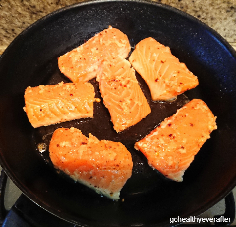 marinated pieces of orange butter salmon being fried in a pan