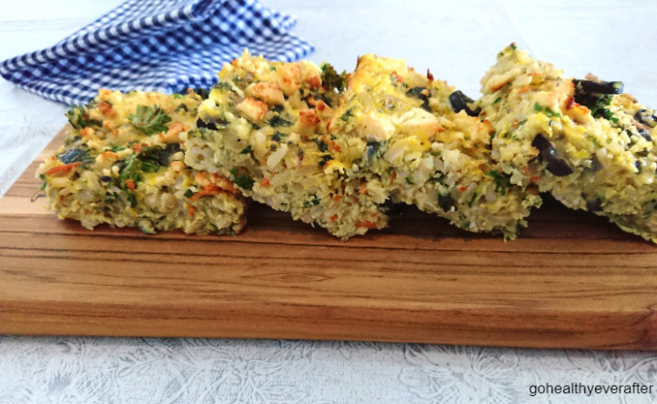 close-up view of slabs of frittata with brown rice, zucchini and feta cheese on a serving board