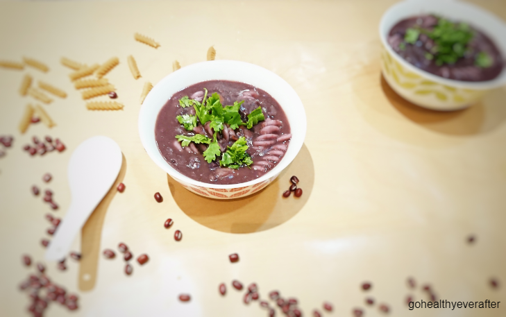 red bean soup with brown rice pasta in a white bowl