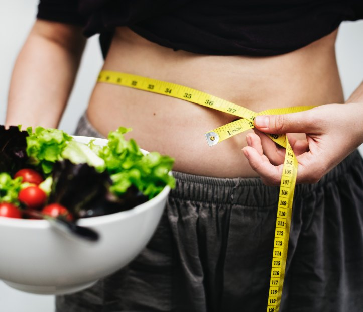 a woman holding a bowl of salad measuring her waist.