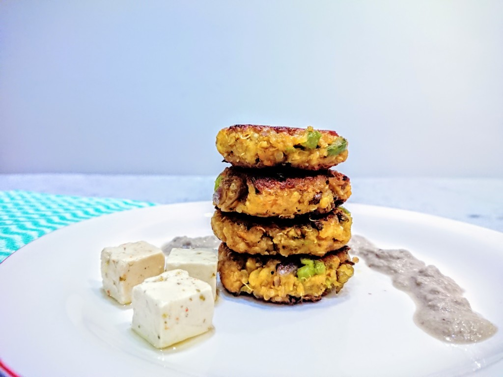 quinoa patties arranged vertically on a plate with coconut walnut sauce and feta cheese cubes