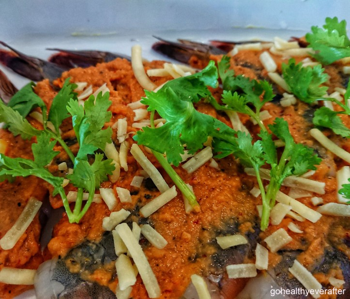 close-up view of tiger prawns in tomato sauce with cheese and cilantro sprinkled on top.