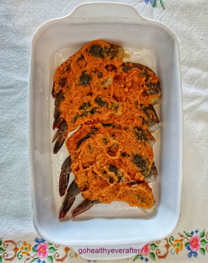 raw tiger prawns with tomato sauce arranged in a baking dish
