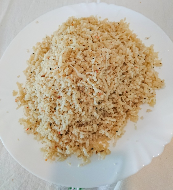 cooked and seasoned cauliflower rice on a white ceramic plate