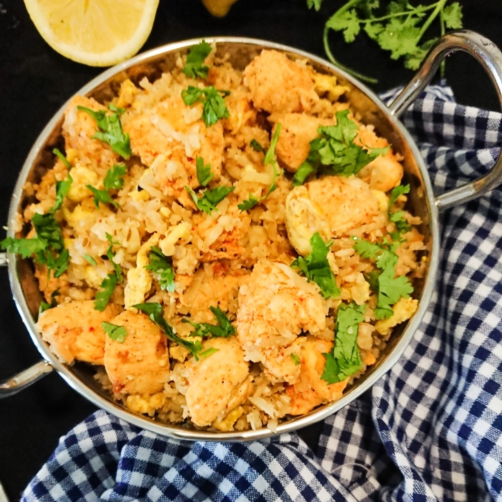 top view of masala chicken cauliflower rice in a silver bowl