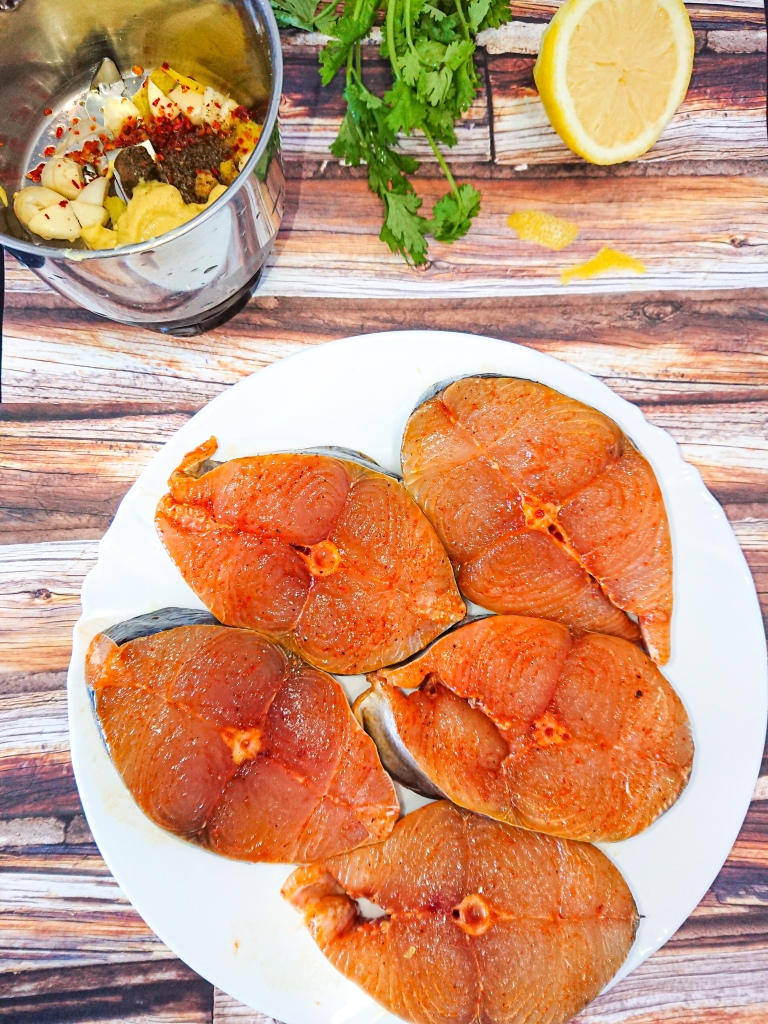 5 marinated fish steaks on a white porcelain plate