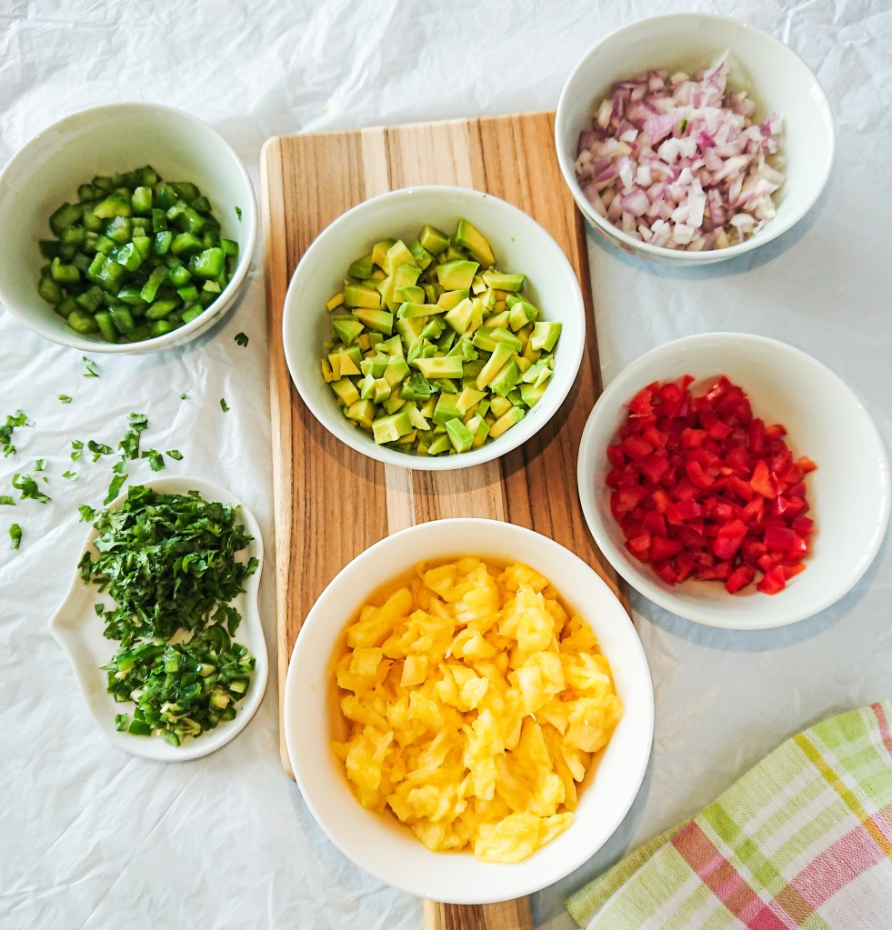 Ingredients for pineapple avocado salsa-finely chopped pineapple, avocado, onion, green and red peppers, jalapeno and cilantro