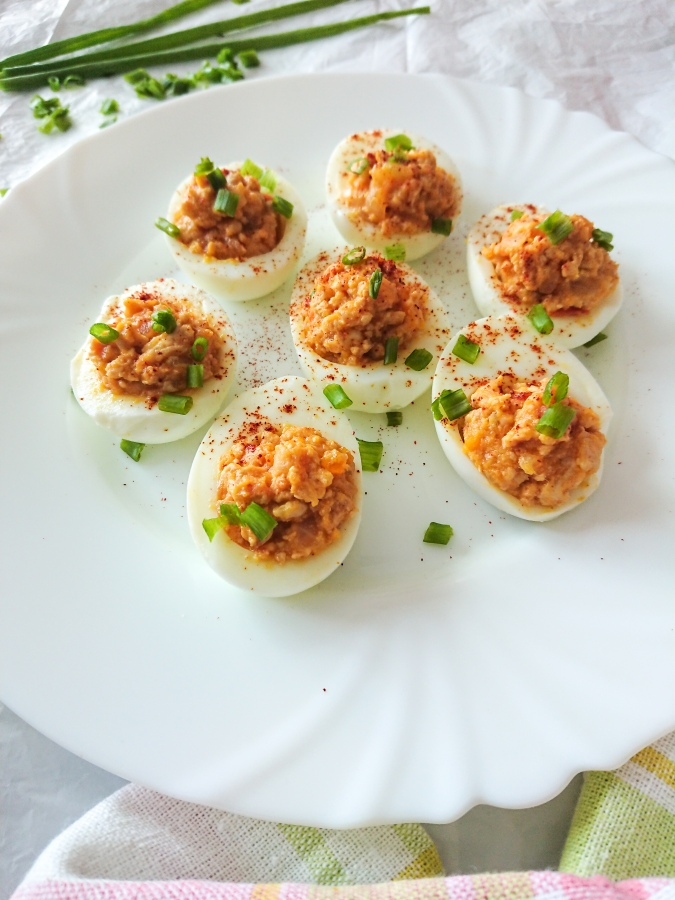 Close-up view of chicken deviled eggs in a white ceramic plate