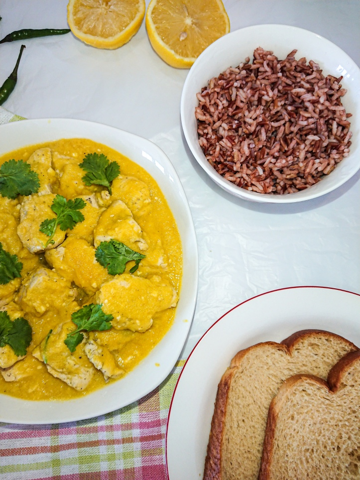 top view of chicken in yellow pepper mustard sauce and a bowl of red rice and brown bread