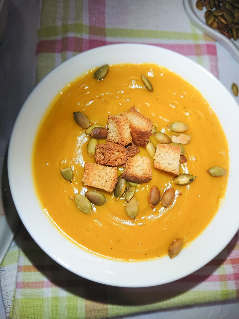close-up view of easy pumpkin soup in a white ceramic bowl garnished with toasted pumpkin seeds and wholegrain croutons.