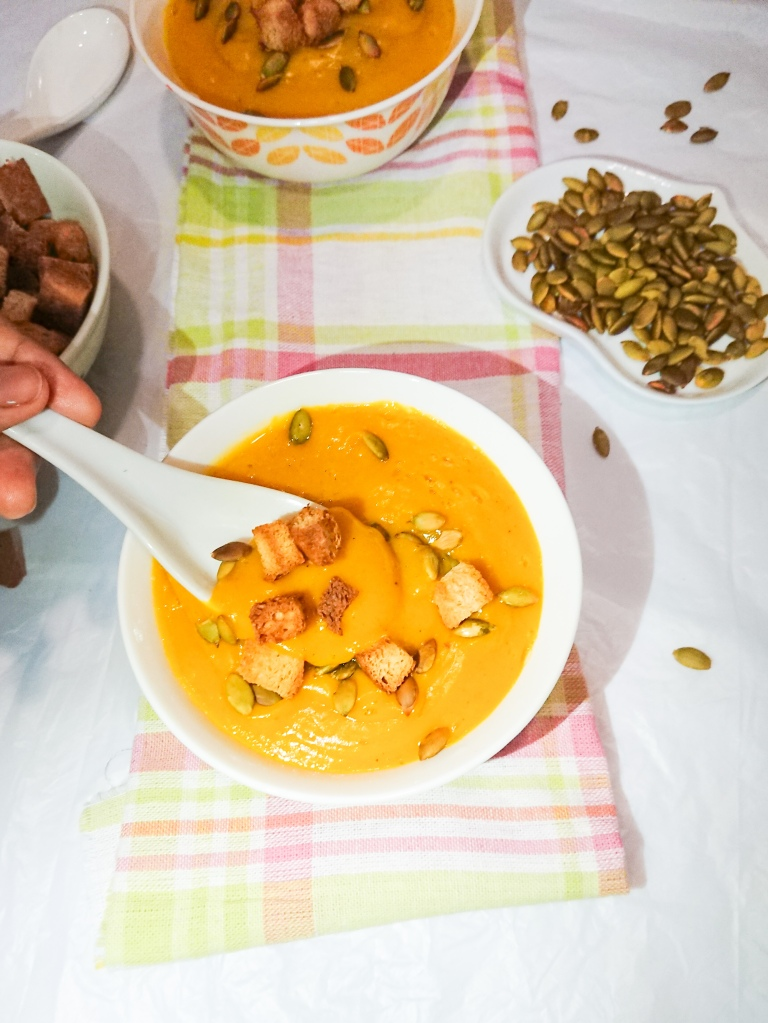 Easy pumpkin soup in 2 white ceramic bowls, toasted pumpkin seeds and wholegrain croutons for garnish