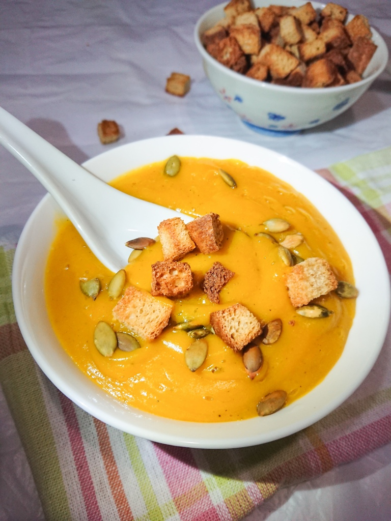 Easy pumpkin soup in a white ceramic bowl garnished with toasted pumpkin seeds and wholegrain croutons.