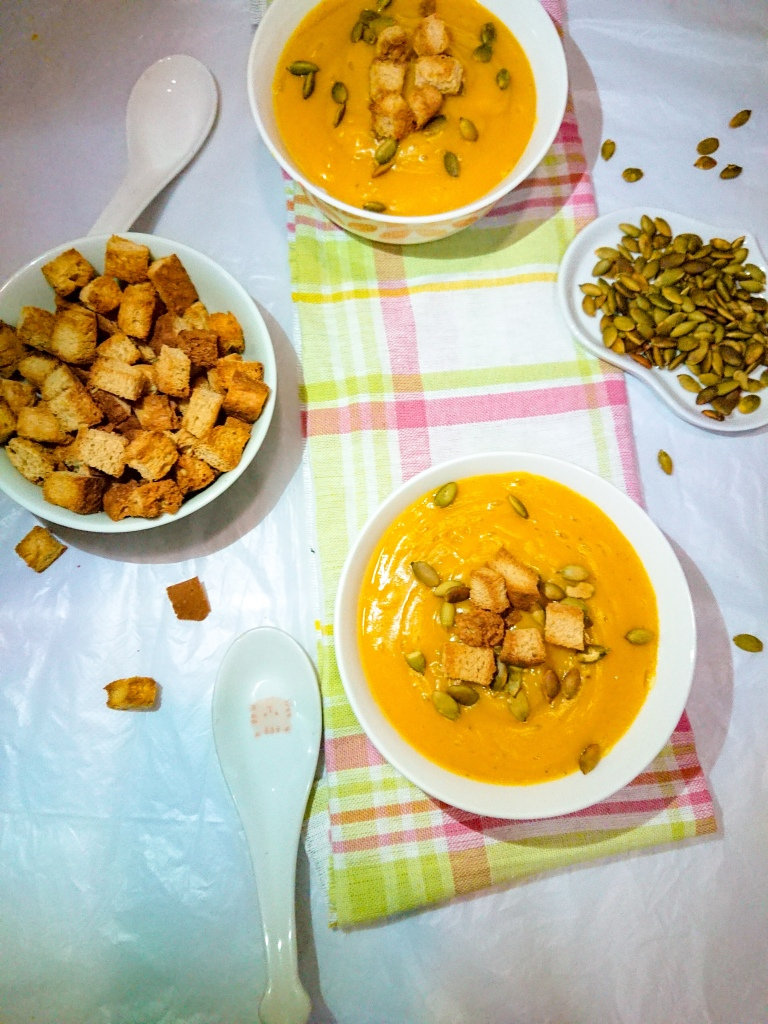 top view of Easy pumpkin soup in 2 white ceramic bowls, toasted pumpkin seeds and wholegrain croutons for garnish